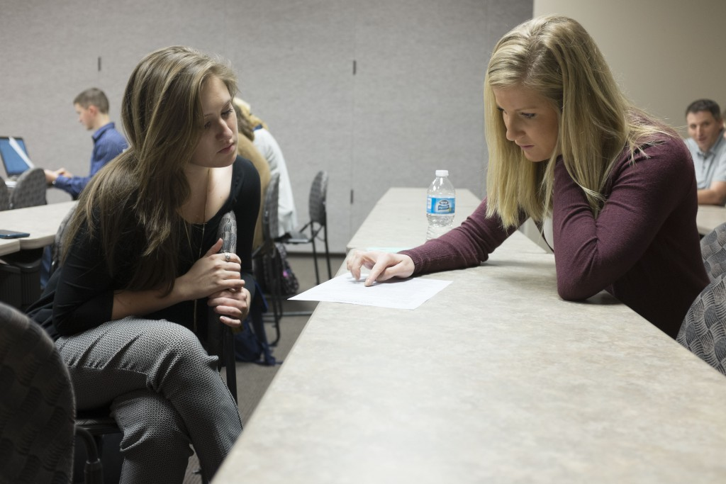 Tabitha Haney Davis ('15) works with a student during a resume building session March 13.