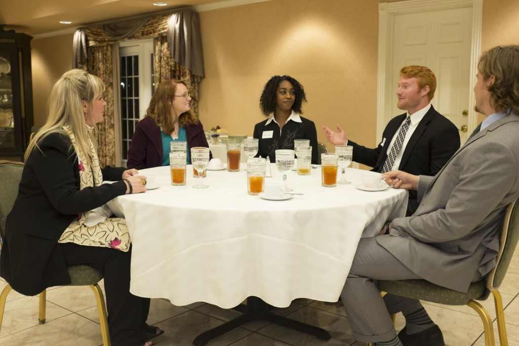 Assistant Professor of Marketing Lori Sloan visits with students at her annual etiquette dinner April 11.